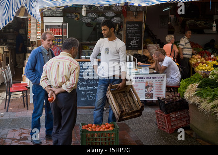 Turkish people traders and shoppers at a fruit and vegetable market stall in Fethiye,Turkey - Stock Photo