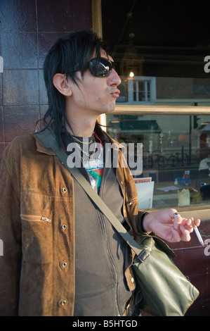 Cool looking man wearing sunglasses and smoking a cigarette, outside the Warwick Castle Pub, Portobello Road, London - Stock Photo