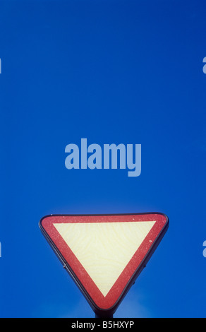Blank red and white upside down triangular roadsign giving advance warning of Give way or Stop line with blue sky - Stock Photo