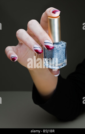 A manicured hand exposing a nail polish bottle. Main manucurée présentant un flacon de vernis à ongles. - Stock Photo