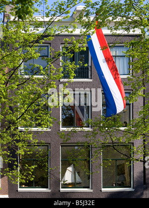 Amsterdam. House on a canal in the Jordaan with Dutch national flag and a model sailing-boat on the windowsill. - Stock Photo