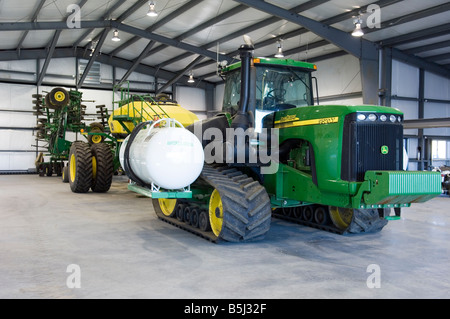 A track tractor with commodity cart and air seeder parked in the shop for maintenance - Stock Photo
