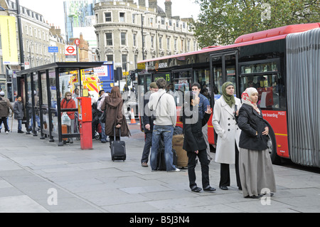 Passengers waiting for bus at bus stop outside Kings Cross Station - Stock Photo