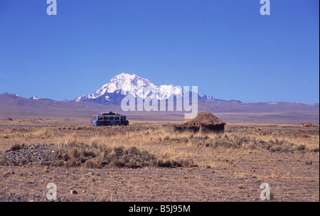 Local bus driving across the altiplano near a rustic hut, Mt Huayna Potosi in background, Bolivia - Stock Photo