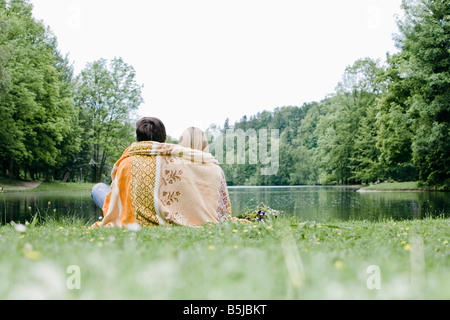 rear view of couple wrapped in blanket sitting at lake in park - Stock Photo