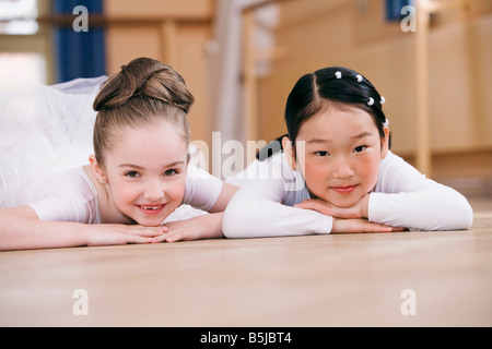 portait of tow young ballet dancers lying on floor - Stock Photo