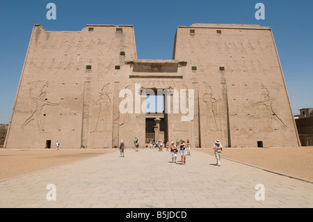 Tourists walking outside Edfu ancient Egyptian temple dedicated to the falcon god Horus, built in the Ptolemaic period between 237 and 57 BCE, Egypt Stock Photo