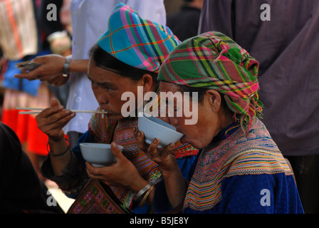 Flower Hmong having a meal at the market of Bac Ha Village Northern Vietnam - Stock Photo