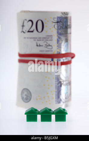 three green houses on front of a wad of 20 pounds sterling bank notes cash tied up in a roll with elastic band - Stock Photo