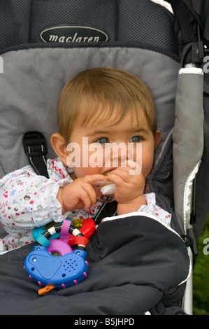 Baby Girl Child sitting sat in a Pushchair Chewing On a Teething Ring - Stock Photo