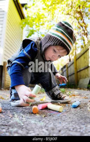 1 year old boy writes with chalk crayons on concrete - Stock Photo