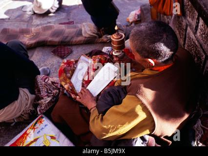 Tibetan monk sitting in street Tibet - Stock Photo