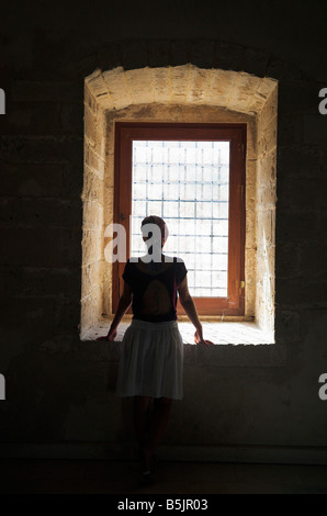 Silhouette of young woman looking out of window - Stock Photo