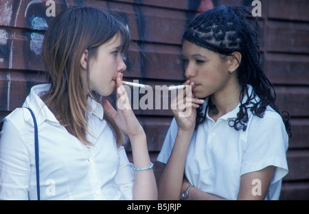 two secondary school girls smoking hiding behind shed - Stock Photo