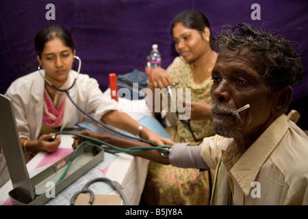 HelpAgeIndia sponsored cardiology health screening patient Mr Murugesan in makeshift lab in warehouse Cuddalore - Stock Photo