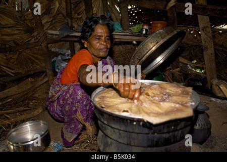 Rasamball makes and sells idly in her bamboo shack at HAI Kandakadu village TamilNadu - Stock Photo