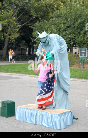 A kid having her picture taken with a mime depicting Lady Liberty at Battery Park, New York - Stock Photo