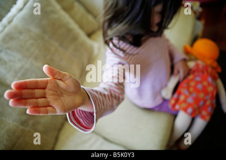 Five year old girl smacks doll - Stock Photo