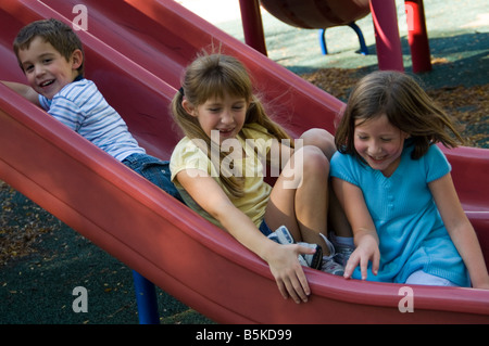 Three young children coming down slide together, smiling and laughing - Stock Photo