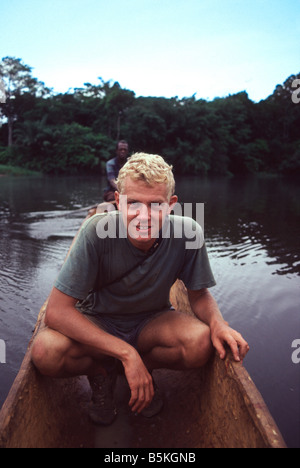 A traveller crosses a small river in Zaire in a wooden dugout canoe - Stock Photo