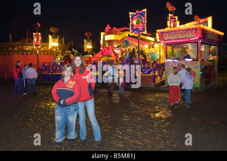 Two young women posing for a night time photograph in front of various rides at a fun fair - Stock Photo