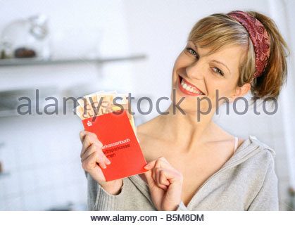young woman standing in the kitchen showing her bankbook - Stock Photo