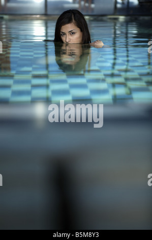A woman in the pool with her head above water. - Stock Photo