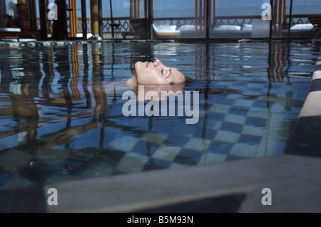 A woman floating in the pool with her face above water. - Stock Photo
