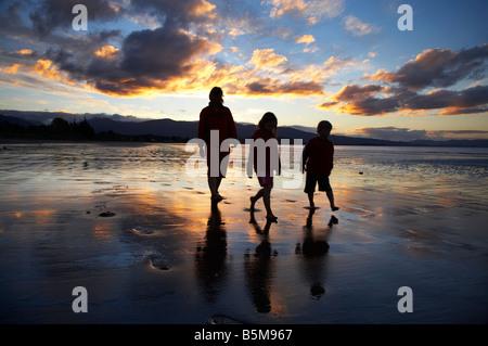 Family Walking Along Beach at Sunset Pohara Beach near Takaka Golden Bay Nelson Region South Island New Zealand - Stock Photo