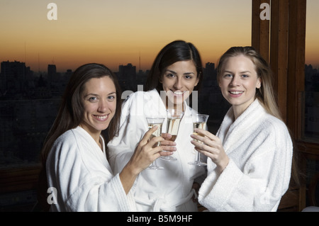 Three women in their robes, drinking champagne. - Stock Photo