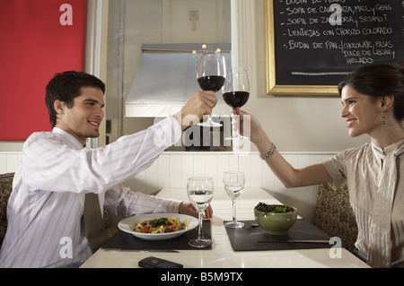 A couple having a toast at dinner. - Stock Photo