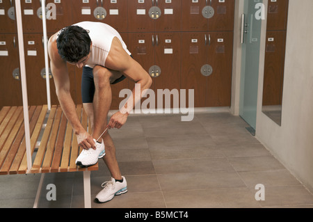 A man tying his shoes in a locker room - Stock Photo