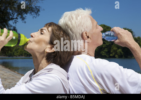 An elderly couple drinking by a lake - Stock Photo