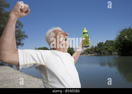 An elderly man with his arms in the air - Stock Photo
