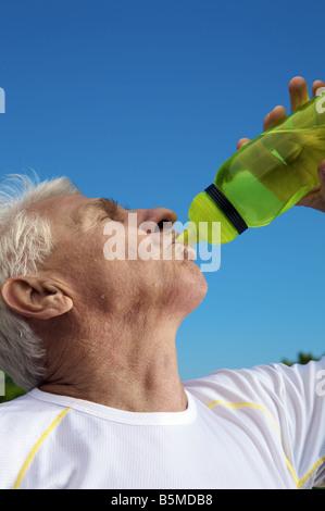 An elderly man drinking from bottle - Stock Photo