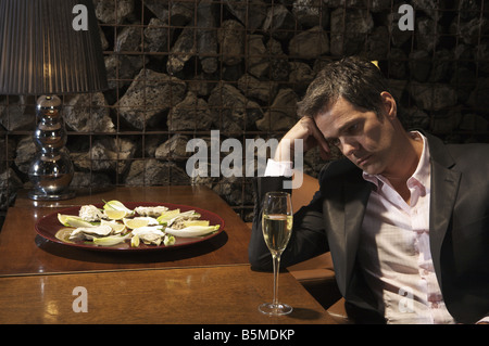 A man staring at a glass of champagne - Stock Photo