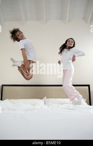A boy and a girl jumping on a bed - Stock Photo
