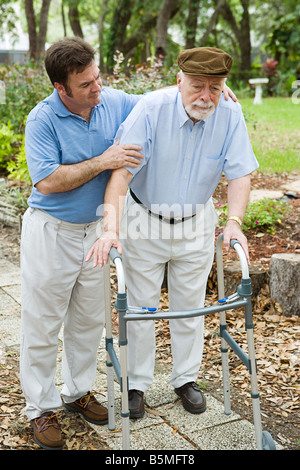 Senior man looks sad as he struggles to walk using a walker His adult son is helping him - Stock Photo