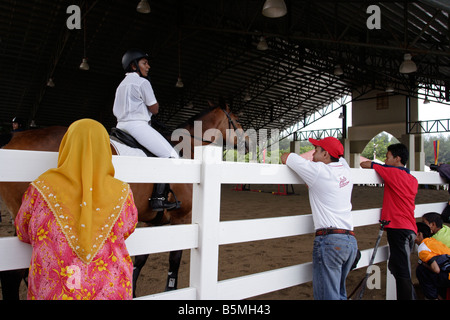 Spectators watching rider warming up the horse before a show jumping competition in Terengganu, Malaysia. - Stock Photo
