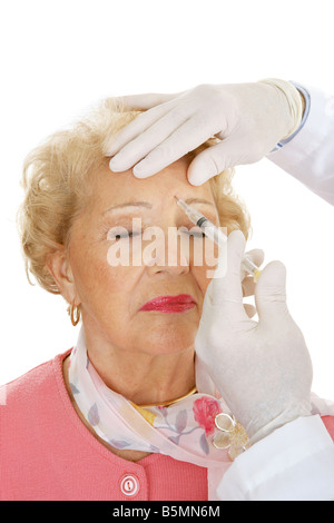 Senior woman getting cosmetic injections to remove forehead wrinkles White background - Stock Photo