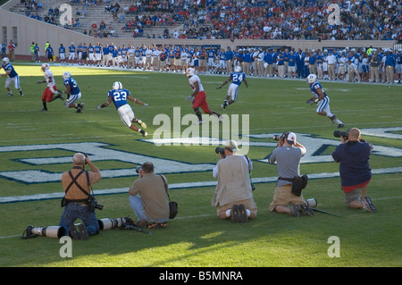 Photographers reporters taking photographs during football game between Duke and North Carolina State University - Stock Photo