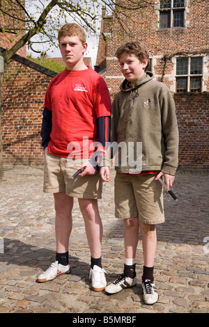 Two boys (probably sons of University lecturers / professors) in a water fight game at the Beguinage of Leuven. - Stock Photo