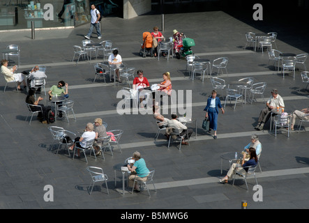 People sitting at outdoor tables on London's South Bank before the National Theatre, London, England - Stock Photo