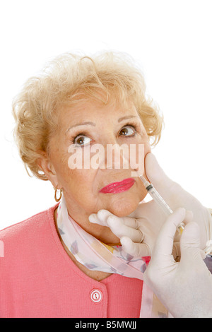 Senior woman getting cosmetic injections in the wrinkles around her mouth White background - Stock Photo