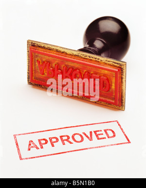 a colour color picture of a red rubber stamp engraved with the word approved - Stock Photo