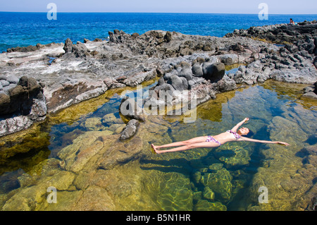 Woman floating in colorful water pool by the sea. Pantelleria Island, Sicily, Italy. - Stock Photo