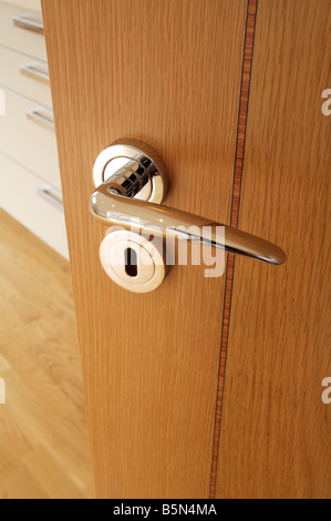 Chrome Plated Door Handle And Escutcheon On An Inlaid Oak Veneered Door In  A Luxury Apartment