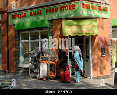 Halal food store with two women talking in doorway, King's Cross, London, England - Stock Photo