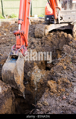 Digging a trench with a digger while preparing the footings to start the building of a new house. - Stock Photo