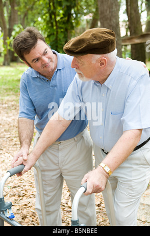Adult son caring for his aging father who is confined to a walker - Stock Photo